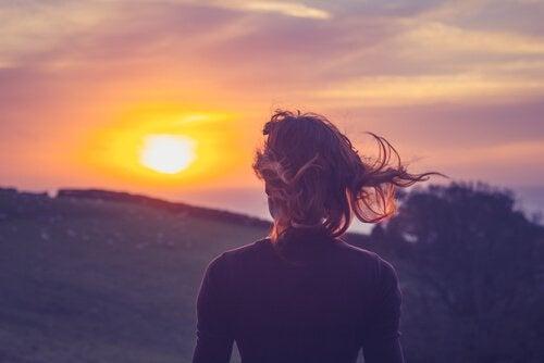 güneşli manzara izleyen kadın