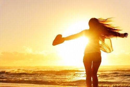 kumsalda elinde kalp tutan arkası dönük kadın