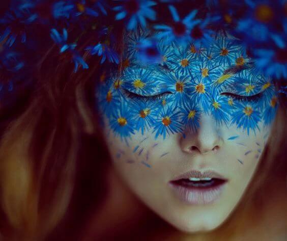 mavi çiçeklerden oluşan maskesi olan kadın