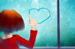 çocuk cama kalp çiziyor