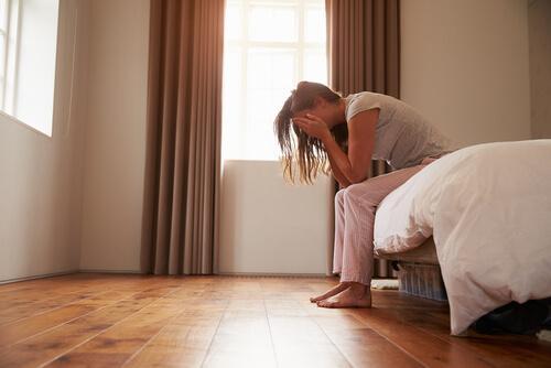 yatakta oturan endişeli kadın