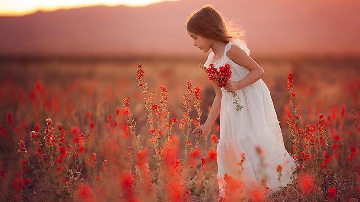 kırmızı çiçekler toplayan beyaz elbiseli kız
