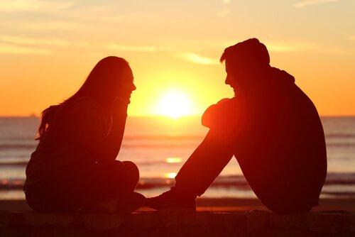 gün batımında deniz kenarında oturanlar