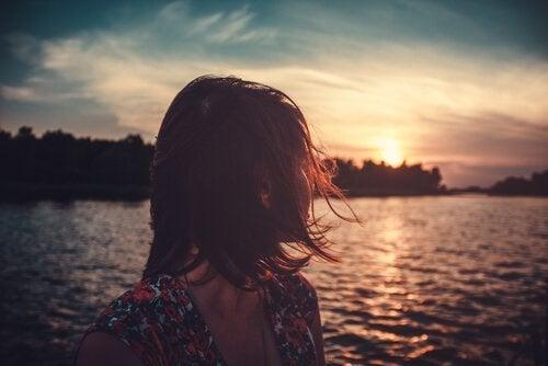 deniz ve güneşe bakan kişi