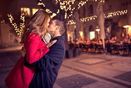 ışıklı sokakta öpüşen çift