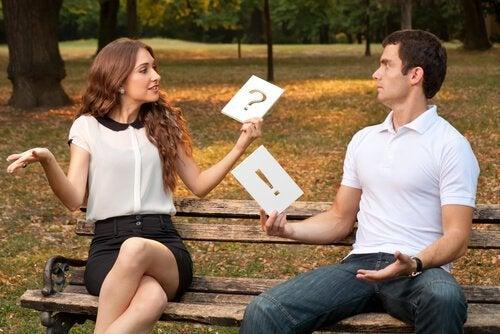 ellerinde soru işareti ve ünlemlerle tartışan çift