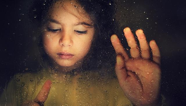 yağmurlu camın arkasındaki üzgün çocuk
