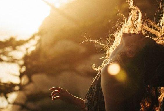yukarıya bakan saçları uçuşan kadın