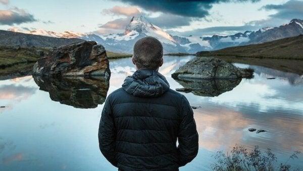 arkası dönük genç adam göl manzarasına bakıyor