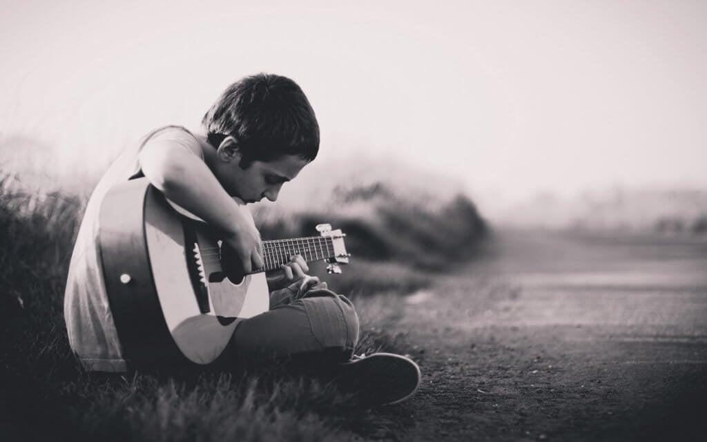 çocuk oturmuş gitar çalıyor