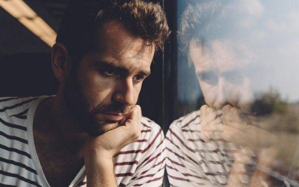 camdan bakan üzgün adam