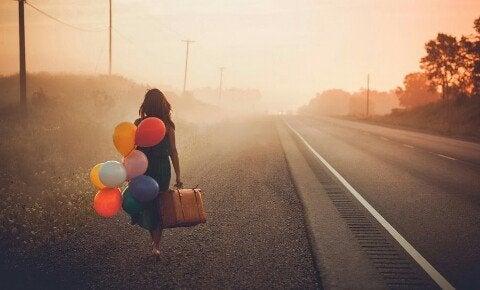 yolda balonlarla yürüyen kişi