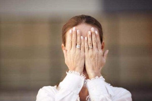 kadın yüzünü elleriyle örtmüi