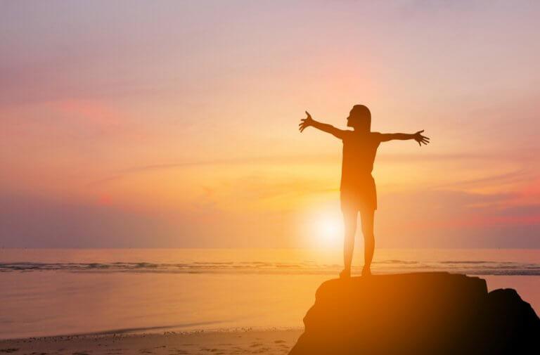 sahilde güneşe kollarını açan insan
