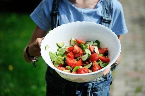 bir kase salata tutan çocuk