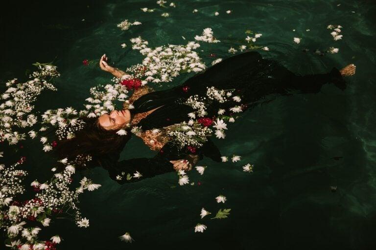 suda çiçeklerle duran elbiseli kadın