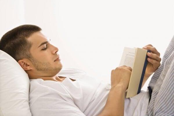 adam yatakta kitap okuyor