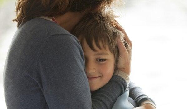 annesine sarılan gülümseyen bir çocuk