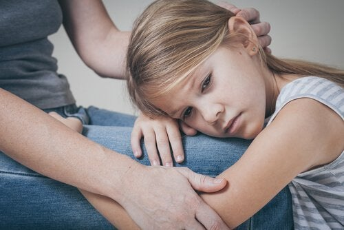 annesinin kucağına kafasını koyan üzgün kız