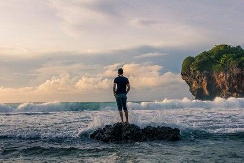 denizdeki kayada arkası dönük duran adam