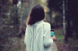 arkası dönük ormanda yürüyen kız