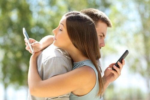 birbirlerine sarılırken telefonlarına bakan çift
