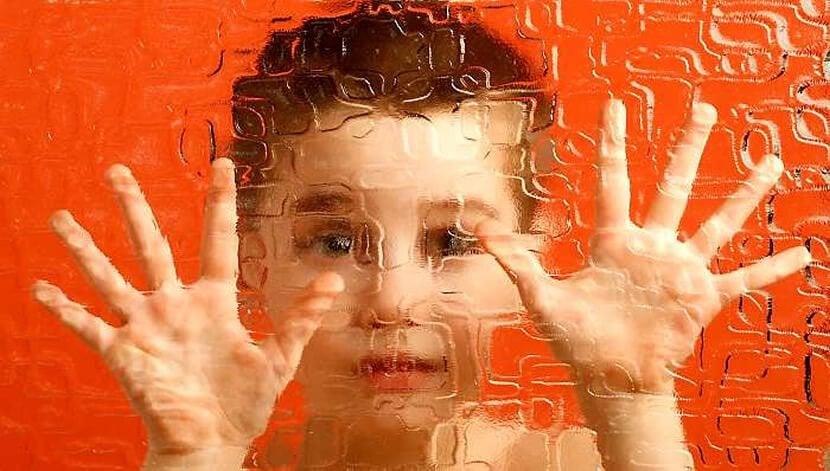 camın üzerine parmaklarını koymış bir çocuk