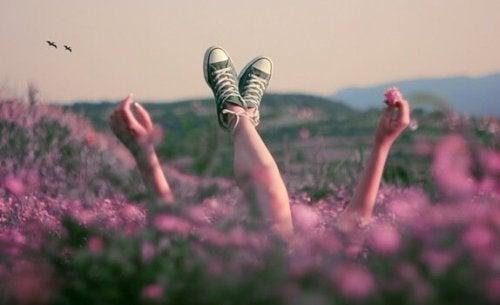 çiçeklerin arasına converse ayakkabılarla uzanmış kişi