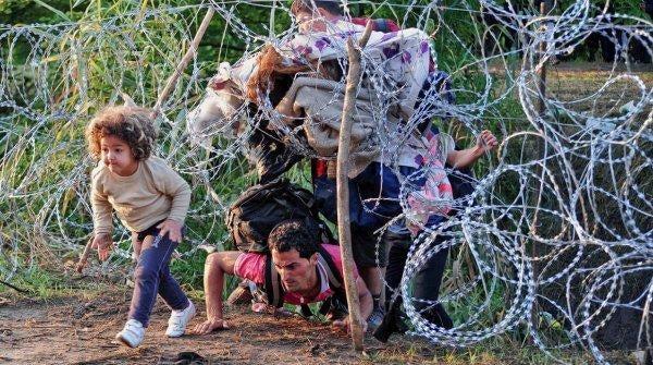 dikenli telleri aşan mülteci baba ve çocuk