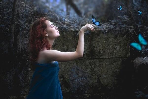 eline mavi kelebek konan kızıl saçlı kadın