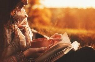 elinde kahve kitap okuyan kadın