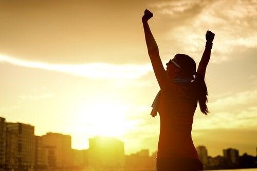 kollarını kaldıran kadın ve gün batımı