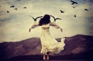 kuşların omuzlarından tuttuğu beyaz elbiseli kadın