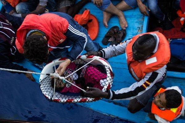 mültecinin bebeğine yardım eden insanlar