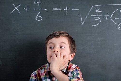 okul tahtasının önünde düşünen çocuk