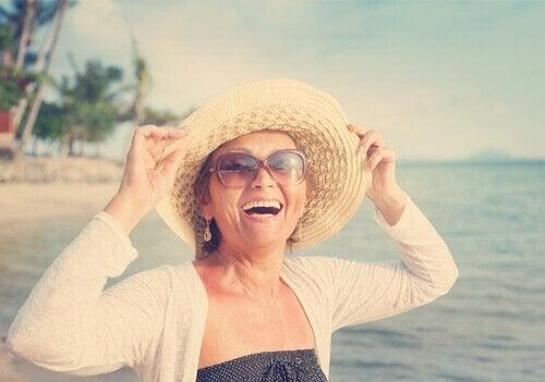 deniz kenarında şapkalı orta yaşlı mutlu kadın