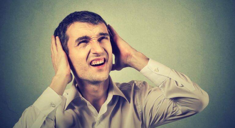 ses yüzünden kulaklarını kapatan adam