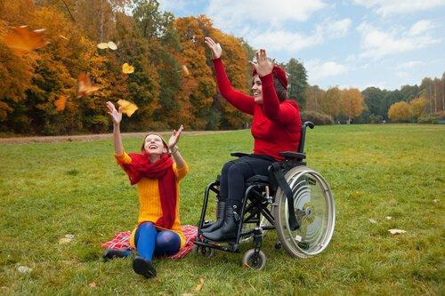 tekerlekli sandalyede bir kadın ve arkadaşı çimlerde