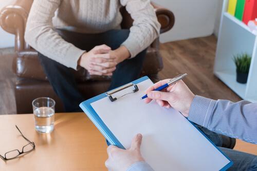 terapist adamı dinleyip notlar alıyor
