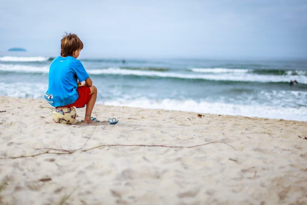 topun üzerinde oturup denizi seyreden çocuk