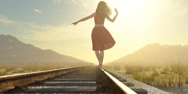 tren yolunda demirin üstünde yürüyen kadın