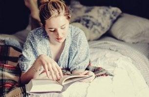 kadın yatakta kitap okuyor