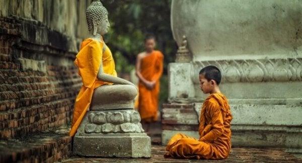 Buda heykeli önünde oturmuş çocuk
