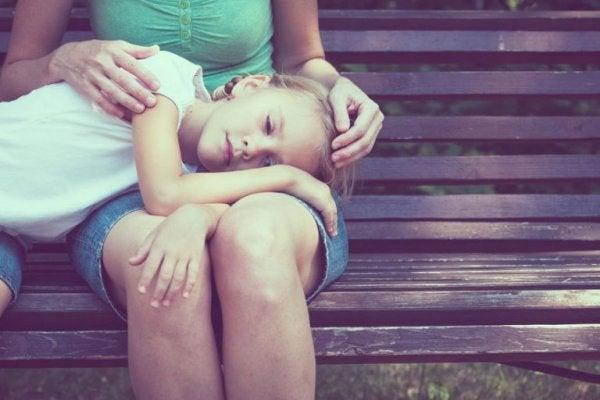 annesinin dizinde yatan çocuk
