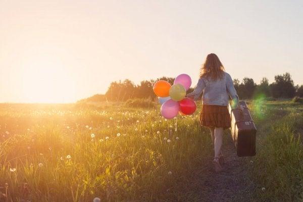 balon ve bavul taşıyan kadın