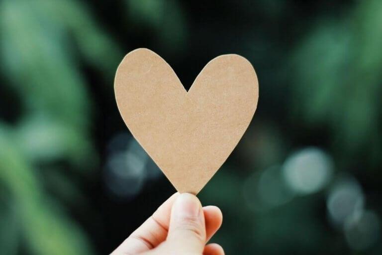 elinde kağıttan kalp tutan parmak