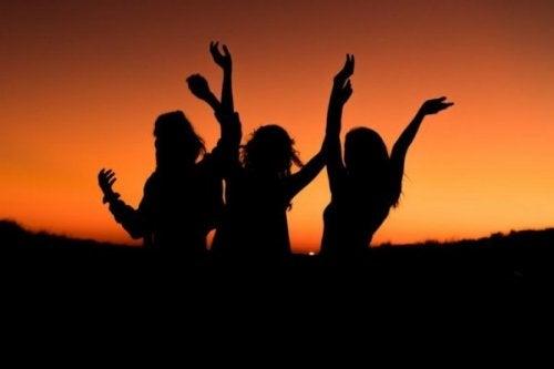 gün batımında dans eden mutlu insanlar