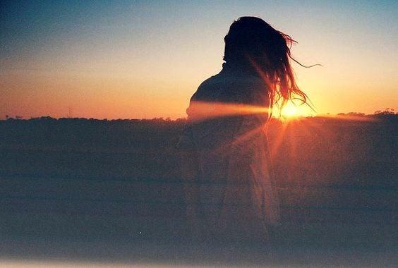 gün batımında oturan kadın