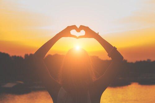 güneşe doğru kalp yapan kadın