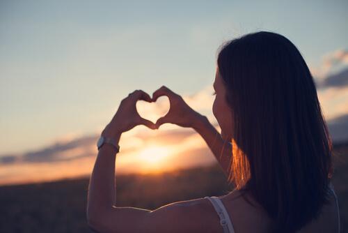 kalp işareti yapan kendini seven kadın